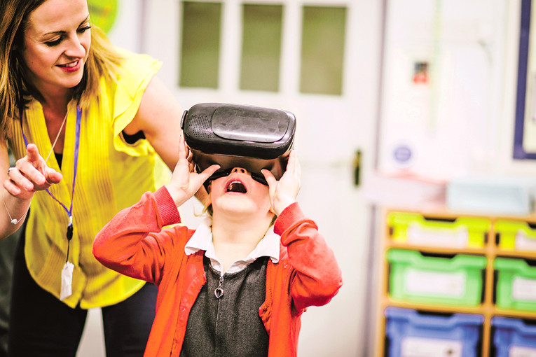 Teacher is helping one of her primary school students use a virtual realtiy headset in the classroom.